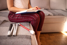 Young Blind Woman Reading Book Written In Braille At Home With White Cane . Blind Person Reading Book Written In Braille. Young Blind Woman Reading A Braille Book While Studying And Sitting At Home