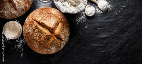 Billede på lærred Traditional sourdough loaf of bread and ingredients for making it on a black bac
