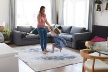 Caucasian Mother And Daughter Having Fun Dancing In Living Room
