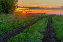 Dirt Road Leading Through The Steppe Wheels Against The Background Of A Not Bright Colorful Dawn.