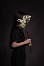 Girl In Black With White Lilac Flower Branch In Dark Painterly Studio Setting