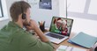 Caucasian man wearing phone headset on laptop video chat during christmas at home