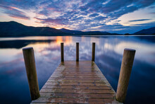 Vibrant Sunset With Dramatic Clouds And Wooden Jetty At Derwentwater Lake In The Lake District, UK.