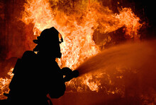 Silhouette Of Firemen Fighting A Raging Fire With Flames. Forest Fire.