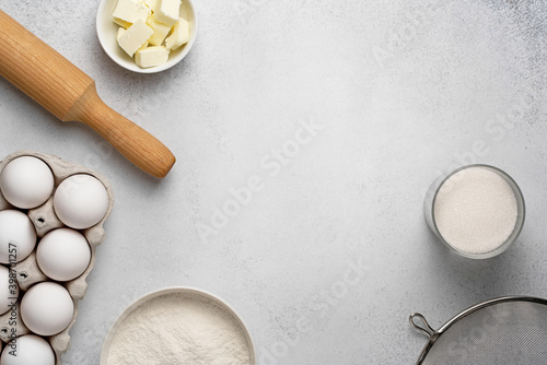 Canvastavla Wheat flour, sugar, sieve, rolling pin, butter and white eggs on grey background