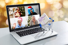 Happy Girl In Santa Hat Gereeting Friends With Christmas In Video Chat On Laptop. Young Woman Lying Under Decorated Pine Tree Among Gift Boxes And Packages In Home Interior With Copy Space