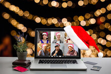 Computer In Cozy Room With Hanging Red Hat And With Santa Claus On Screen Wishing Merry Christmas And Happy New Year Online