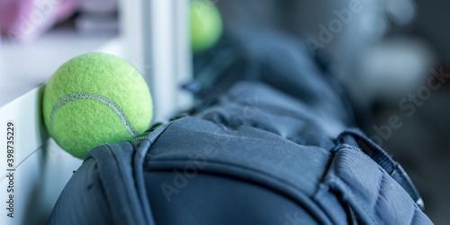 Fototapeta Tennis ball laying on big blue tennis player bag in sport change room