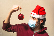 Young Man Wearing A Red Christmas Hat With Stars, Blue Pandemic Face Mask And Red Hoodie Looking A Red Brilliant Christmas Ball. White Background. Scene Of New Normality During Covid-19 Pandemic.