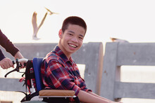 Asian Disabled Child On Wheelchair Smiling In The Outdoors nature And Seagull Birds Background ,Life In The Education Age Of Special Children, Happy Disability Kid Travel In Family Holiday Concept.