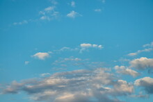 Light Blue Sky, With Small Tufts Of White Clouds Floating And Shaded Clouds On The Horizon.