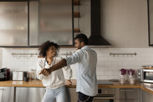 Excited Young African American Couple Have Fun Enjoy Early Morning In Modern Renovated Kitchen. Happy Millennial Biracial Man And Woman Dance Celebrate Moving Relocation To Own Home. Realty Concept.