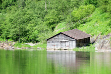 Picturesque Old Wooden Boat Sheds On The River With Forest On The Background