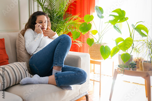 Fototapeta Young woman caller talking on the phone at home
