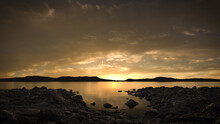 Peaceful Lake Scene At Sunset Or Sunrise With A Cloudy Sky Reflecting In The Still Water. A Calm, Tranquil And Serene, Natural Landscape.