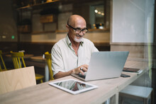 Mature Caucasian Man In Spectacles Typing On Laptop Computer Share Content In Blog Browsing Web Pages And Information, Successful Male Freelancer Doing Remote Job Using Netbook In Coworking Space