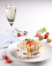 Desserts. Pavlova. Meringue With Cream, Fresh Strawberries, Mango Sauce And A Glass Of Champagne On A White Table With Forks. Menu Cafe. Background Image, Copy Space, Vertical