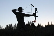 Silhouette Of American Bow Hunter Drawing Bow Back In Woods
