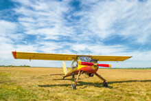 Small Old Yellow And Red Plane Standing In Summer Field Front View