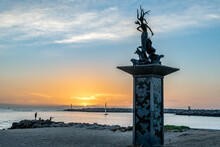 Ventura Harbor Mouth Entrance Has Mermaid Statue Ushering The Lone Sail Boat Back Into The Safety Of Harbor As Sun Sets Behind Island Horizon Of Pacific Ocean.
