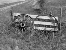 A Horizontal Photo Of Old Wagon Wheels Leaning On A Wooden Gate.
