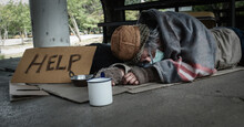 A Homeless Man In A Face Mask Lays On The Ground With His Mug. He Is Unemployed And Hungry Due To The Coronavirus Epidemic.