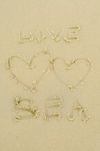 Handwritten Love Sea Text With Two Hearts On Sand