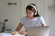 Close up wearing headphones writing notes, using laptop, studying online at home, motivated young student learning language, watching webinar, listening audio course, e-learning education concept