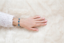 Young Adult Woman Hand Touching White Fluffy Fur Blanket. Flower Bracelet On Female Wrist. Closeup. Top Down View.