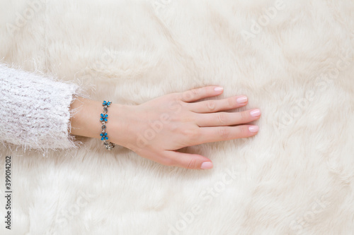 Photo Young adult woman hand touching white fluffy fur blanket
