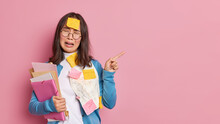 Stressed Unhappy Female Student Cries From Desprair Being Fed Up Of Exam Preparation Points Away On Blank Space Overloaded With Papers Has To Remember Much Information Isolated On Pink Wall.