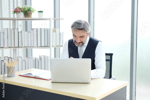 Photo Smiling Smart Caucasian senior manager and businessman in black suit is working with laptop at workspace in modern office