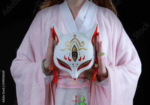 Valokuva Woman wearing kimono and a fox mask