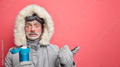 Wondered man spends time outdoors during blizzard and very cold day drinks hot beverage from thermos dressed in warm outerwear indicates aside on blank space attracts your attention to something
