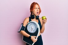 Young Beautiful Redhead Woman Holding Weight Machine To Balance Weight Loss Angry And Mad Screaming Frustrated And Furious, Shouting With Anger. Rage And Aggressive Concept.