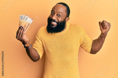 Fototapety, obrazy: Young african american man holding 500 norwegian krone banknotes screaming proud, celebrating victory and success very excited with raised arm