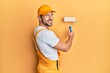 Leinwandbild Motiv Young caucasian painter smiling happy painting wall using roller.