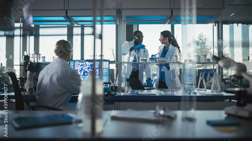 Fototapeta Medical Science and Biotechnology Laboratory with Diverse Team of Research Scientists Working. Microbiologist and Biochemist Talking About Newly Done Test, Using Micropipette. obraz na płótnie
