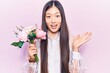 Young beautiful chinese woman holding pink bouquet of flowers celebrating achievement with happy smile and winner expression with raised hand