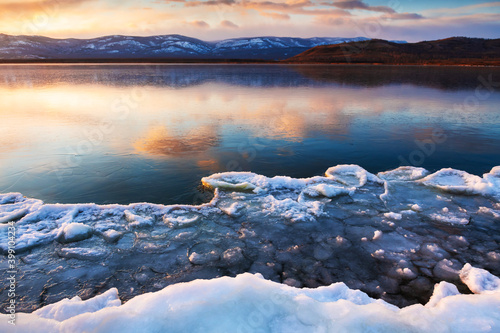 Obraz Ice on the frozen lake at sunset. Mountains and sky are reflected in the ice surface of the lake. Beautiful winter landscape. South Ural, Russia - fototapety do salonu