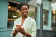 Leinwandbild Motiv Young african american businesswoman smiling happy using smartphone at the city.