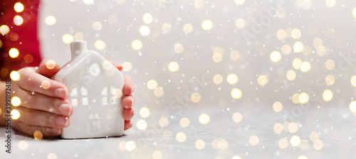 Fototapeta Women hands hold a new small ceramic house with windows with copy space. Golden lights holiday background obraz