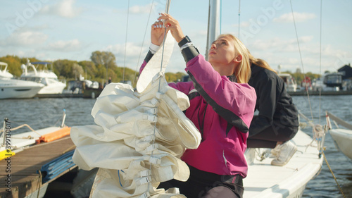 Canvas Print A young blonde with a teammate puts the mainsail on the afterstay of her sports yacht