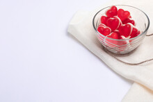 Gelatin Hearts In A Glass Transparent Saucer And Dried Flowers With Hare Tails On A White Background And A Brick Wall. Valentine's Day Banner.