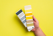 Palette With Color Of The Year 2021 - Ultimate Gray And Illuminating Yellow In Man's Hand. Trendy Color Swatches
