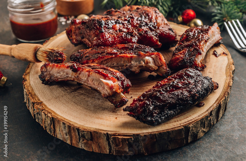 Fototapeta Homemade barbecued ribs seasoned with a spicy basting sauce and served with fresh arugula on a wooden board. Christmas festive background. Selective focus obraz