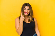 Young Indian Woman Isolated On Yellow Background Pointing With Finger At You As If Inviting Come Closer.