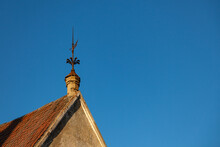 Metal Weather Vane On The Tiled Roof Of An Old House