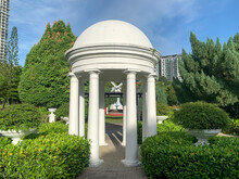 A White Monumental Gazebo At A Park In Kuala Lumpur, Malaysia. Trees And Green Leaves Surround It.