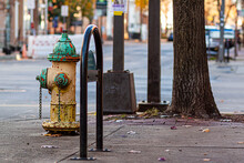 A Rusty, Vintage Fire Hydrant On Side Of A Road On The Sidewalk With Chipped Yellow And Green Paints On It. In The Blurred Background There Is A Street View At An Urban Location.